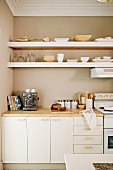Fitted kitchen with white base units and white floating shelves against beige-painted wall in traditional interior