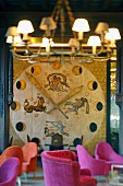 Enormous, floor-to-ceiling clock with phases of moon and zodiac applied to wall; armchairs with pink upholstery in foreground
