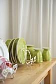 Fröhliches Geschirr in Pastellgrün mit weissen Pünktchen auf Holztisch