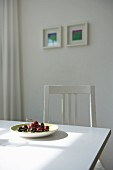 Plate of fresh cherries on white dining table in sunny kitchen