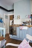 Blaue Landhausküche mit Gasherd und Spülstein aus Keramik