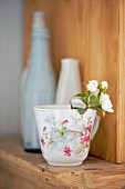 Sprig of roses in vintage cup with floral pattern