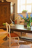 Table lamp and bouquet on solid wooden table and antique chair on rustic brick floor