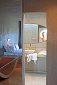 Concrete as predominant material in minimalist hotel room with ensuite bathroom; interesting arrangement of mirror images