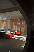 Purist hotel lounge with straw mats and bright red accents combined with grey exposed concrete and rectangular sofas