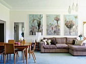 Dining area with wooden retro chairs and couch against wall below floral paintings in living room with stucco frieze running around edge of ceiling