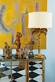 Antiques and table lamp on mirrored, semi-high cabinet in front of modern image on wall