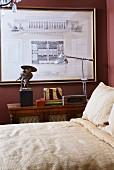 Bett mit Leinenbettwäsche in Naturfarben vor Retro Stehleuchte und gerahmte Architekturzeichnung an dunkelroter Wand