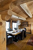 Chairs with dark loose covers around set table next to windows in log cabin