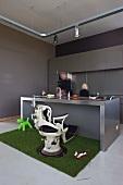 Old dentist's chair in front of counter in minimalist designer kitchen