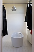 Purist bathroom with free-standing bathtub and industrial-style pendant lamp; dark clothing on clothes hangers hung on metal rod