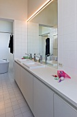 Minimalist washstand in front of large wall-mounted mirror in white bathroom