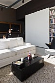 Sunny interior with black-painted travelling trunk as coffee table in front of white sofa