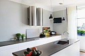 Free-standing kitchen island with sunken sink below pendant lamp and kitchen counter along wall with futuristic extractor hood