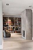 Minimalist interior with open-plan fireplace in concrete wall opposite armchair in front of fitted bookshelves