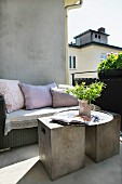 Sunny balcony with modern concrete cubes as side tables in front of rattan bench with cushions against house facade
