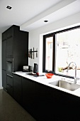 Kitchen counter with black fitted cupboards against wall with window