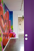 View through open purple door into modern hall with colourful graffito mural