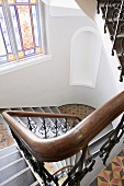 Traditional stairwell with stained glass window and patterned tiled floor