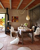 Simple wooden table and white plastic shell chairs below teardrop-shaped pendant lamp in simple country house with ribbed ceiling