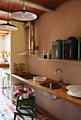 Simple, floating kitchen counter with wooden worksurface and sink mounted in niche below vintage lanterns on floating shelf in retro-style, open-plan interior