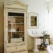 Glass-fronted, vintage-style cabinet and framed, unplastered section of brick masonry above pedestal sink