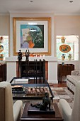 Living room with fireplace, decorated with sculptures, modern painting and decorative ceramic objects