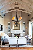 Elegant lounge area with open fireplace below wrought iron candle chandelier hanging from wooden roof structure