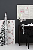 Bolt of fabric and artwork next to partially visible chair and table against black wall with pale pinboard