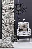 Roll of Toile de Jouy wallpaper on black wall next to armchair; black pendant lamp in foreground
