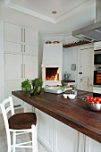 Central island with wooden worksurface and bar stool in white kitchen with open fire