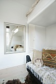 Loft bed and sofa in corner of room next to wall-mounted mirror