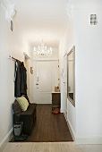 Coat rack in narrow hall with traditional chandelier hanging from ceiling