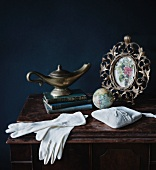 Gloves and evening bag in front of antique oil lamp and framed photograph on antique cabinet against black background
