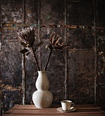 Dry flowers in white porcelain vase and teacup against wall clad in vintage-look metal panels
