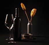 Wine bottle next to wine glass and silver dish in front of vase of artificial flowers against a dark background