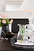 Carafe and glasses on vintage metal tray in front of vase of flowers and table lamp with white fabric lampshade