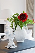 Red flower in vase and porcelain candlestick in front of table lamp on dark tabletop