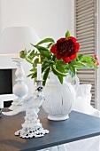 Vase mit roter Blume und Porzellankerzenständer vor Tischlampe auf dunkler Ablage