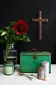 Vintage kitchen utensils in front of green metal case and red flower in vase and cross hanging on black wall