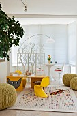 Child's desk with classic chairs, knitted poufs and play rug; white, retro play area behind a floral screen