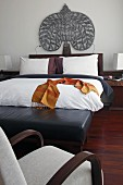 Double bed with ethnic ornamentation above headboard and black leather bench at foot in hotel room