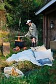 Lager mit Kissen und Felldecke vor einem Unterstand im Wald; Frau mit Hut und umgehängter Decke an einem Feuertopf