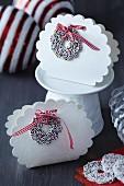 Weihnachtliche Geschenkverpackung aus weisser Pappe in Wolkenform und Zuckerkringel