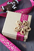 Pink ribbon with pattern of stars and cardboard bow on gift box