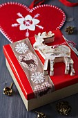 Gift box festively decorated with wooden reindeer pendant and reindeer-patterned ribbon