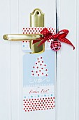 Cardboard Christmas door sign, red bauble and bow on brass door handle