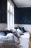 Blue and white patterned scatter cushions and seat cushions on bench below window and blue patterned wallpaper