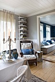 Silver candelabra on table in front of armchair in corner of room with view of living room through open doorway