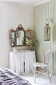 Curved console table with white curtains and wall-mounted, gilt-framed mirror in corner of wood-clad room